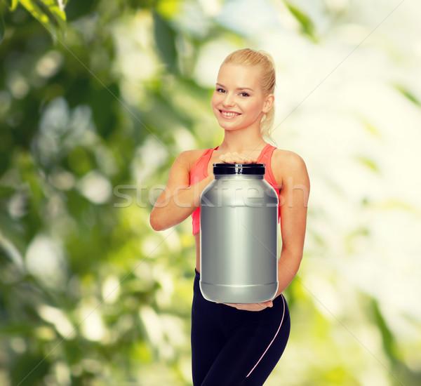 笑みを浮かべて スポーティー 女性 jarファイル タンパク質 フィットネス ストックフォト © dolgachov