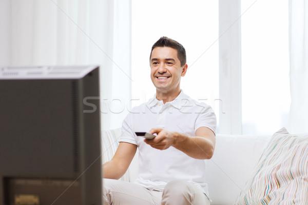 ストックフォト: 笑みを浮かべて · 男 · リモコン · を見て · テレビ · ホーム
