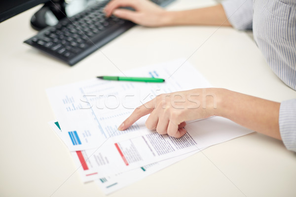 Stock photo: close up of woman hands with papers and computer