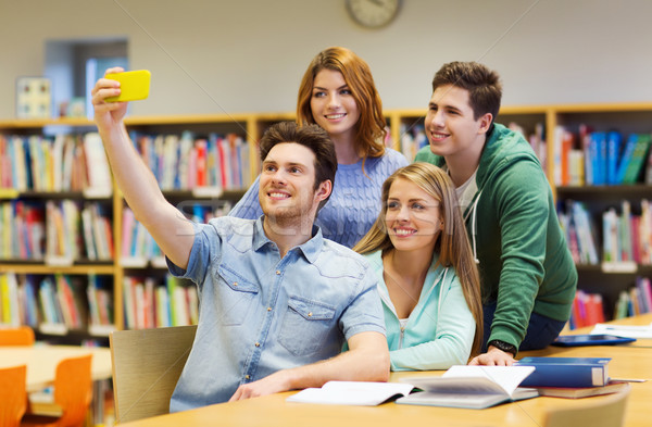 students with smartphone taking selfie at library Stock photo © dolgachov