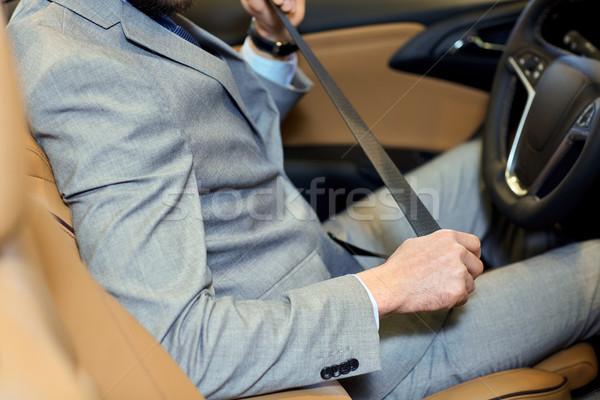 close up of man fastening seat safety belt in car Stock photo © dolgachov