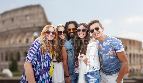 happy hippie friends with selfie stick at coliseum Stock photo © dolgachov