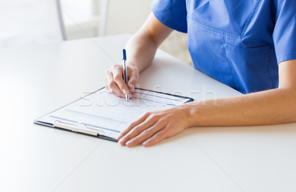 Stock photo: close up of doctor or nurse writing to clipboard