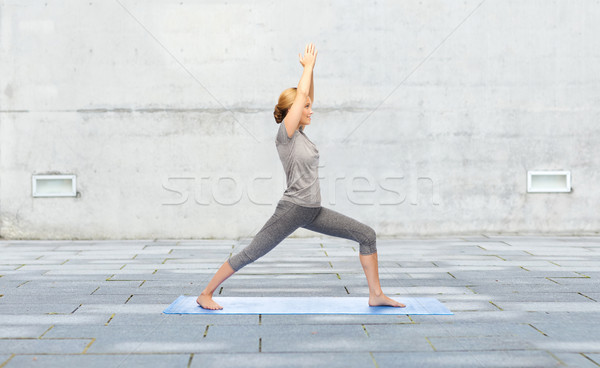 woman making yoga warrior pose on mat outdoors Stock photo © dolgachov