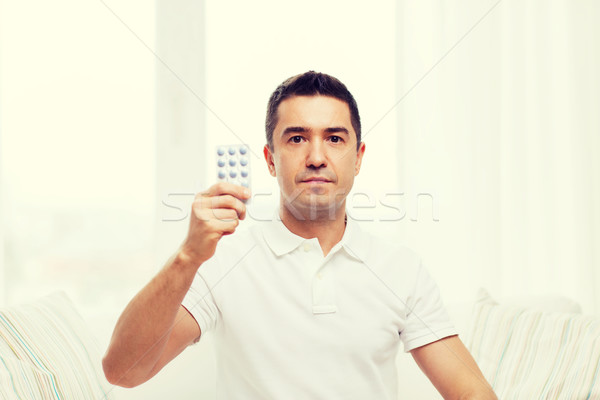man showing pack of pills at home Stock photo © dolgachov