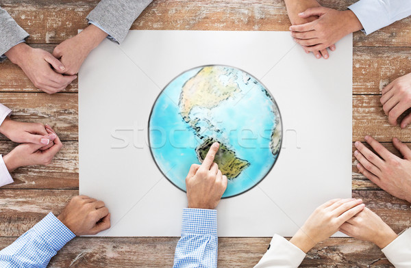Stock photo: close up of hands with globe picture at table
