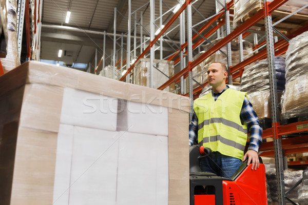 man with tablet pc operating forklift at warehouse Stock photo © dolgachov