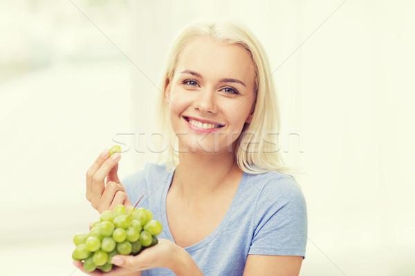 Boldog nő eszik szőlő otthon egészséges étkezés Stock fotó © dolgachov