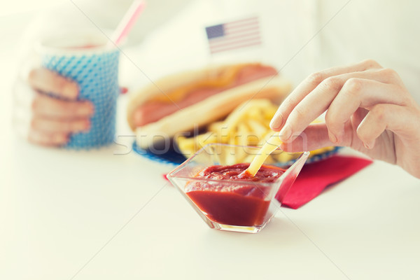 close up of woman hands eating on american food Stock photo © dolgachov