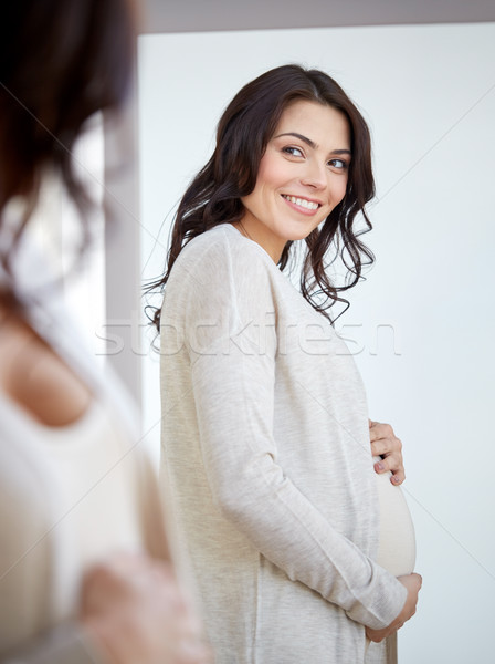 happy pregnant woman looking to mirror at home Stock photo © dolgachov