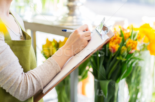 close up of woman with clipboard at flower shop Stock photo © dolgachov