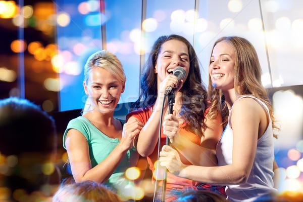 three happy women singing on night club stage Stock photo © dolgachov