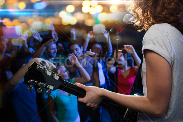 female singer playing guitar over happy fans crowd Stock photo © dolgachov