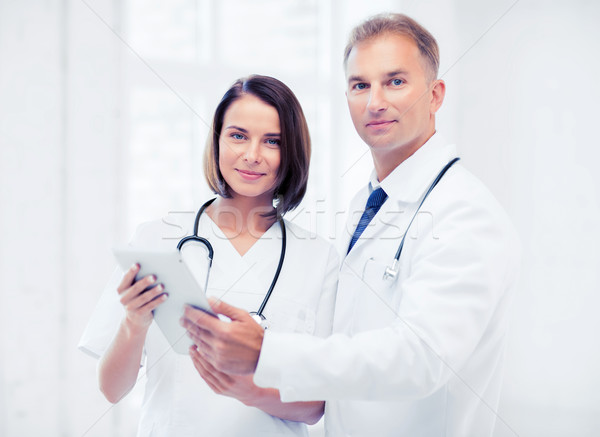 two doctors looking at tablet pc Stock photo © dolgachov