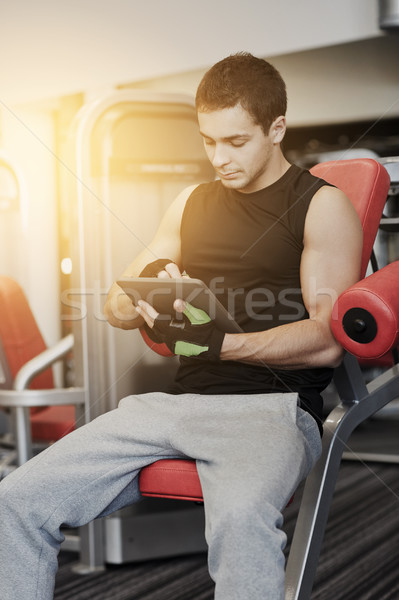 young man with tablet pc computer in gym Stock photo © dolgachov