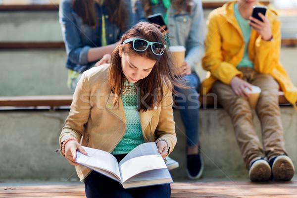 high school student girl reading book outdoors Stock photo © dolgachov
