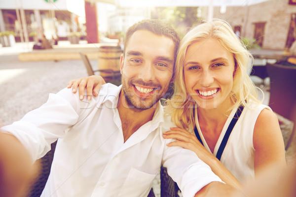 happy couple taking selfie at restaurant terrace Stock photo © dolgachov