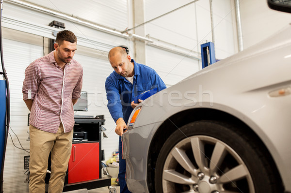 auto mechanic with clipboard and man at car shop Stock photo © dolgachov