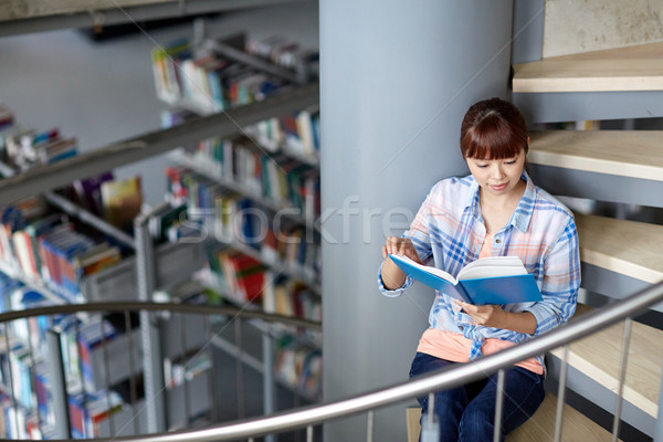 Stock photo: high school student girl reading book at library