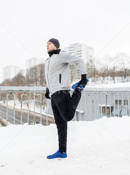 man exercising and stretching leg on winter bridge Stock photo © dolgachov