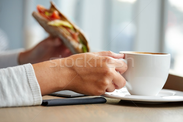 woman drinking coffee and eating sandwich at cafe Stock photo © dolgachov