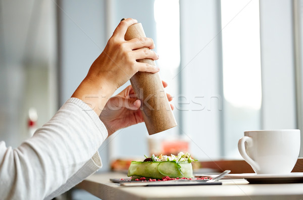 woman with salt shaker and salad at restaurant Stock photo © dolgachov
