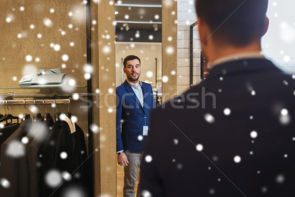 man trying jacket on at mirror in clothing store Stock photo © dolgachov
