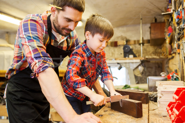 boy and dad with calipers measure wood at workshop Stock photo © dolgachov