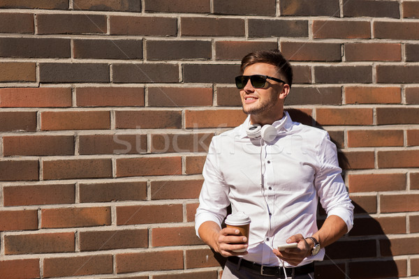 man with smartphone and coffee cup on city street Stock photo © dolgachov