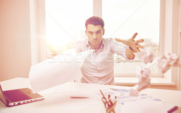 angry businessman throwing papers in office Stock photo © dolgachov