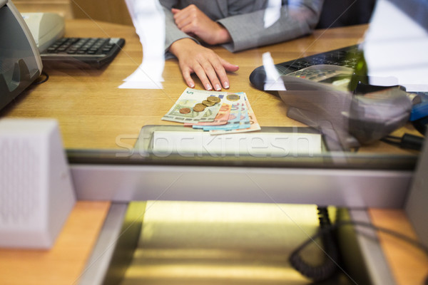 clerk with cash money at bank office or exchanger Stock photo © dolgachov