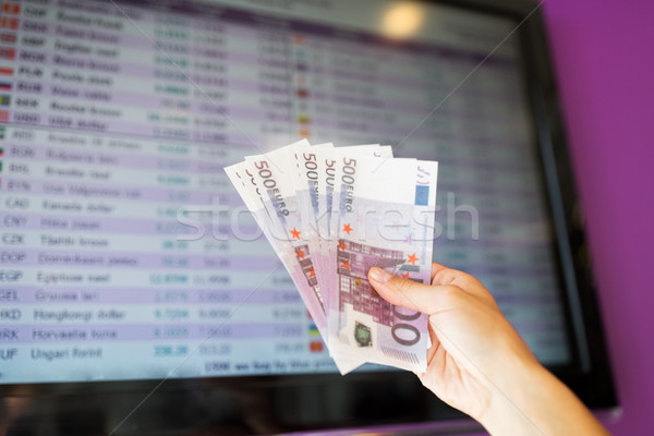 hand with euro money over currency exchange rates Stock photo © dolgachov