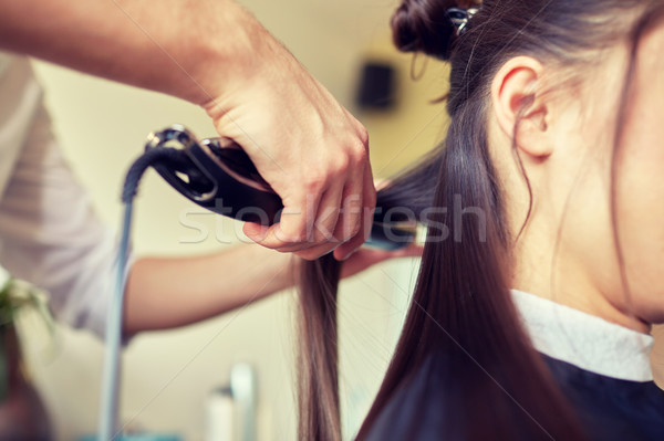 stylist with iron straightening hair at salon Stock photo © dolgachov