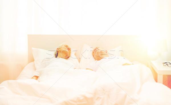 happy senior coupler lying in bad at home Stock photo © dolgachov