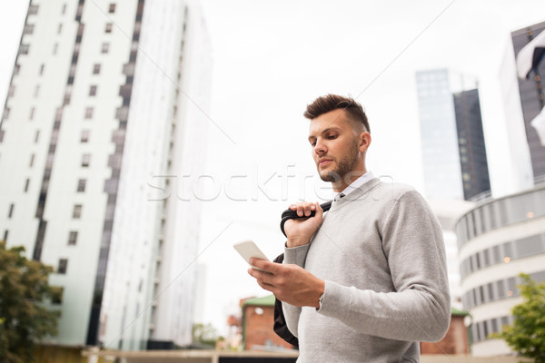 Fiatalember táska sms chat okostelefon város üzlet Stock fotó © dolgachov