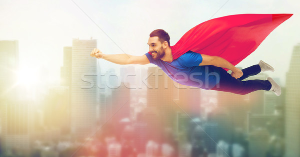 happy man in red superhero cape flying on air Stock photo © dolgachov