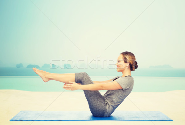 woman making yoga in half-boat pose on mat Stock photo © dolgachov