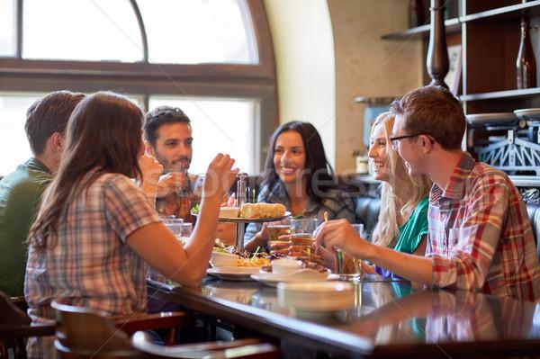 Szczęśliwy znajomych jedzenie pitnej bar publikacji Zdjęcia stock © dolgachov