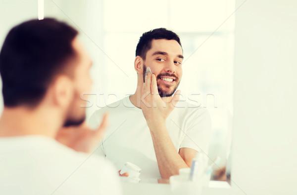 Szczęśliwy młody człowiek krem twarz łazienka Zdjęcia stock © dolgachov