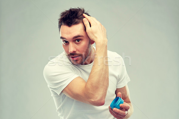 happy young man styling his hair with wax or gel Stock photo © dolgachov