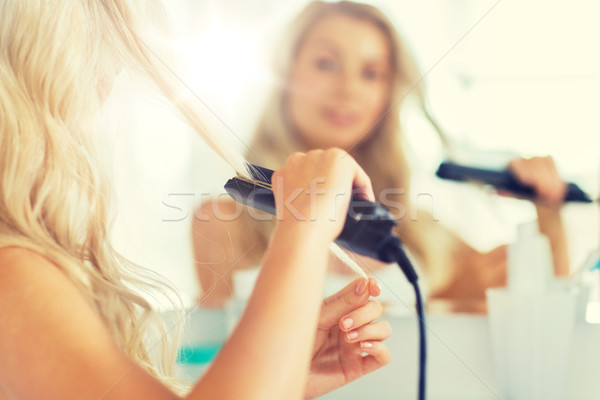 woman with styling iron straightening hair at home Stock photo © dolgachov