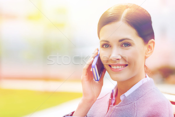 Stock photo: young smiling businesswoman calling on smartphone