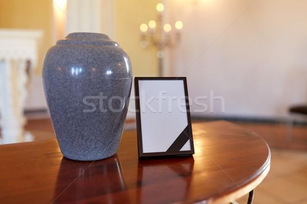 photo frame with mourning ribbon and cremation urn Stock photo © dolgachov