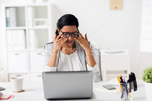 businesswoman rubbing tired eyes at office Stock photo © dolgachov