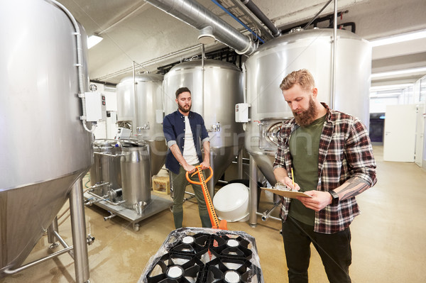 men with beer kegs on loader at craft brewery Stock photo © dolgachov