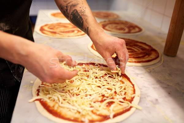 cook adding grated cheese to pizza at pizzeria Stock photo © dolgachov