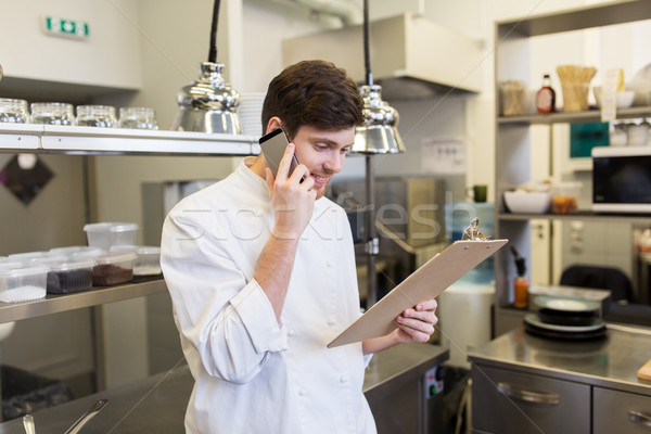 chef cook calling on smartphone at restaurant kitchen Stock photo © dolgachov