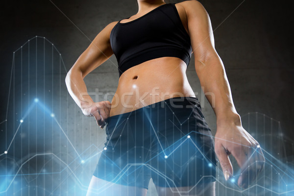 Stock photo: young woman body in gym