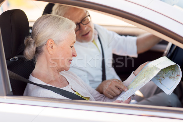 happy senior couple with map driving in car Stock photo © dolgachov