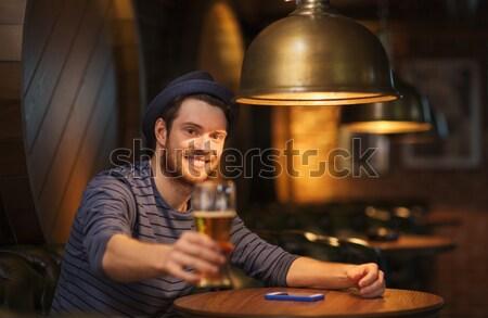smiling man drinking green beer at bar or pub Stock photo © dolgachov